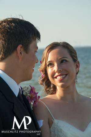 Happy bride looking into grooms eyes on the coast of Lake Erie in Toledo, Ohio.